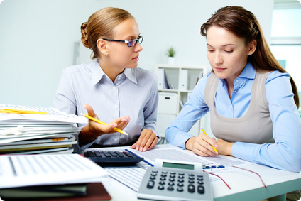 Portrait of young businesswomen interacting while working with papers in office
